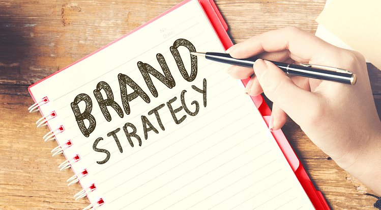 The words brand strategy written in a spiral notebook. Cm2 Media blog on the basics of Brand Strategy for your business.